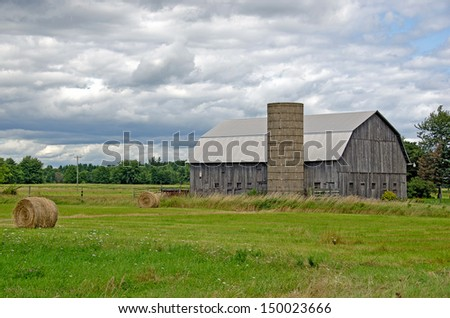 old barn and silo with hay bales