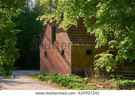 Old barn house of red bricks, with small iron windows, lying in the outskirts of a danish forest, paths of gravel are leading by - stock photo