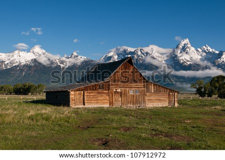 Old Barn in Front of Grand Tetons - stock photo