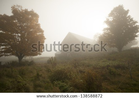 Old barn in the early morning fog during fall foliage season, Stowe Vermont, USA - stock photo