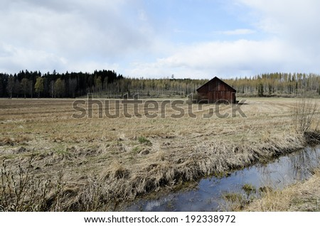old barn is standing in the field, Finland - stock photo