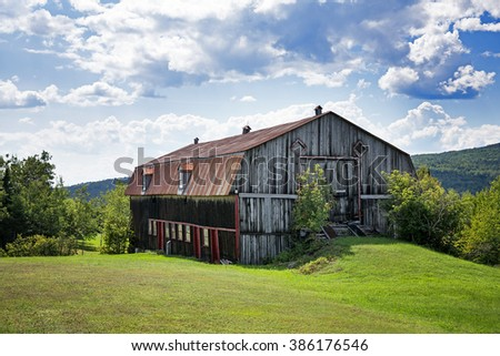 Old barn, La Malbaie, Quebec Province, Canada. Image take from public road. - stock photo