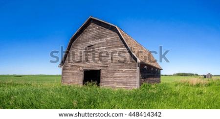 Old barn on the prairies in Saskatchewan on a summer day.  - stock photo