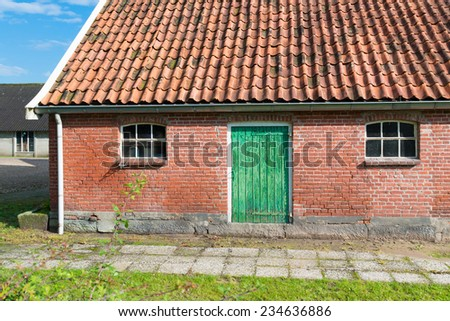 old barn with green door and small windows