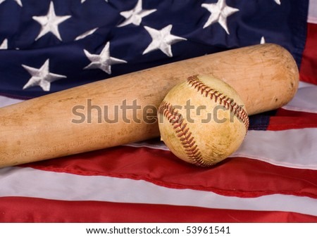 Old baseball and and bat with American flag. Focus is on ball. - stock photo