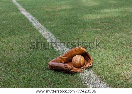 Old baseball and baseball glove lying on the foul line on a baseball field. - stock photo