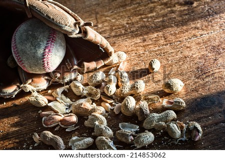Old baseball and glove with peanuts on a weathered wood background. Processed for bleached retro toning. Copy space. Concept: baseball, ballpark, snacks, fans, summer, traditions. - stock photo