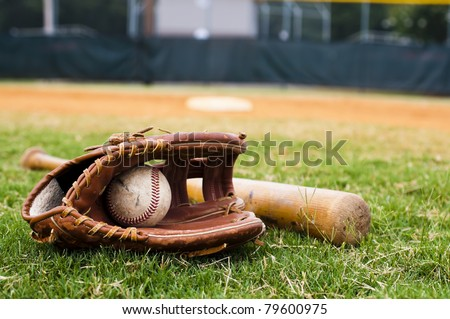 Old baseball, glove, and bat on field with base and outfield in background. - stock photo