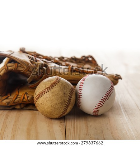 Old baseball glove with baseball on wood background