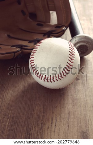 Old baseball with mitt and bat with vintage style filter applied to image - stock photo