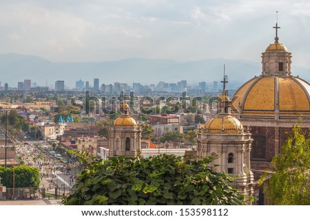 Old Basilica of Guadalupe with Mexico City skyline behind it - stock photo