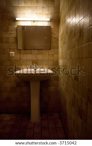 Old bathroom. Natural red tint from light and old walls. - stock photo