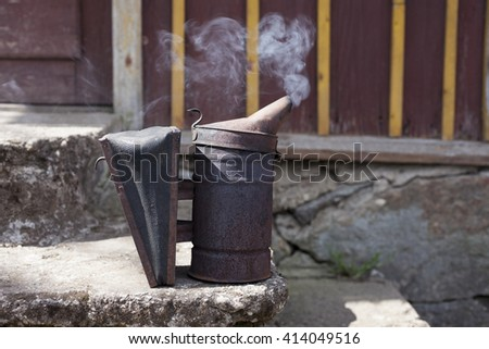 Old bee smoker at staircase, with smoke in the air, ready for using  - stock photo