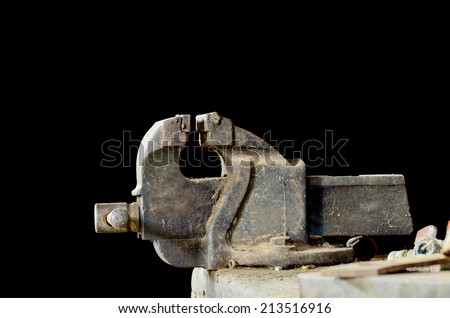 old bench vise at a workshop on black background - stock photo