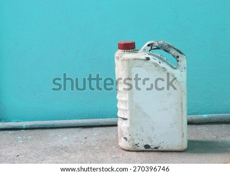 old benzine gallon  on blue wall - stock photo