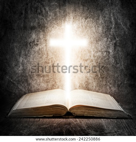 Old Bible and illuminated cross - stock photo