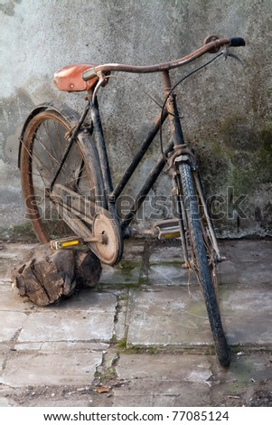 Old bicycle against a dilapidated wall