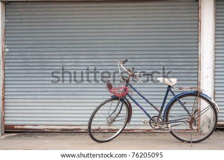 old bicycle at grunge metal door - stock photo