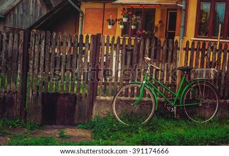 Old bicycle near a fence - stock photo