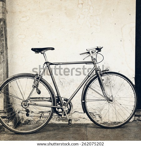 Old bicycle near the wall. Aged effect was applied. - stock photo
