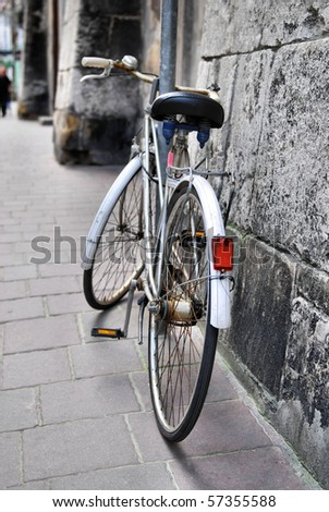 old bicycle on city street, vintage look - stock photo