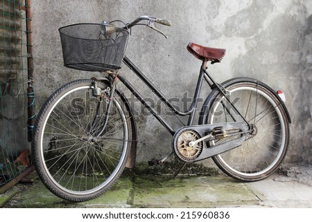 old bicycle over a shabby background - stock photo