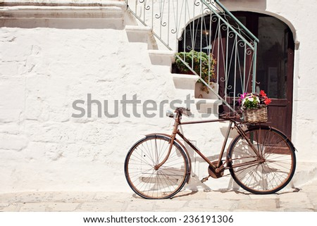 Old bicycle with a basket leaning against a wall in Italy - stock photo
