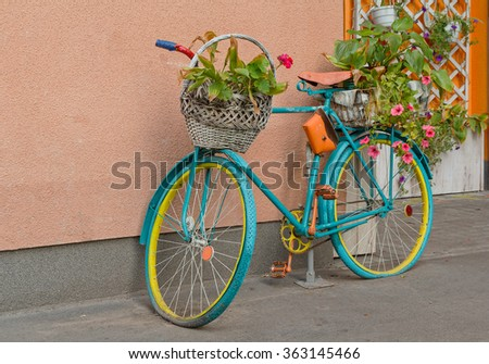 Old bicycle with flowers and a basket by the wall. Decor - stock photo