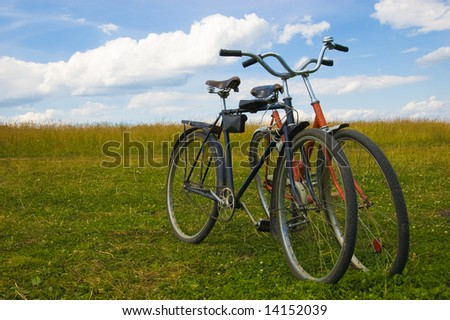 Old bicycles stand on a grass - stock photo