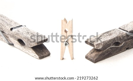 Old big clothespins against some more small and new ones isolated on a white background. - stock photo