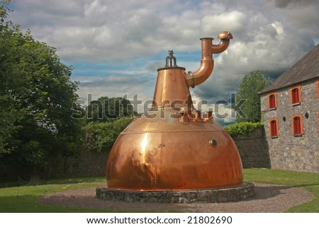 Old big copper whiskey distillery on stone foundation outdoor - stock photo