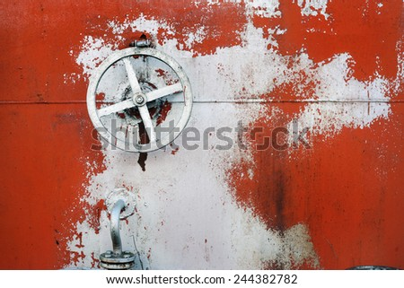 old big hand wheel on the wall of oil tank - stock photo