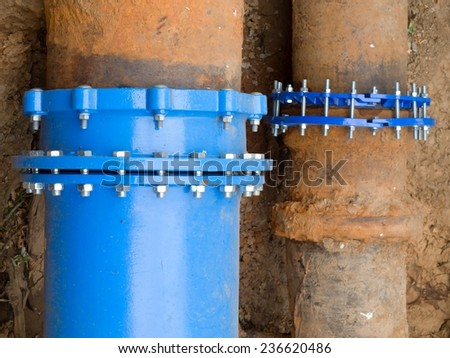 Old big rusty drink water pipes joined with new blue flanges and screws  - stock photo