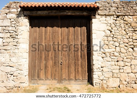 old big wooden doors closed, the wall around is built with stones