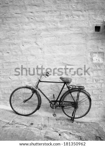 Old bike leans up against a bright blue brick wall in black and white - stock photo