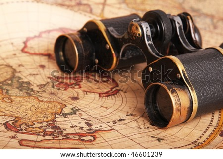 Old binoculars on antique map. Shallow depth of field - stock photo