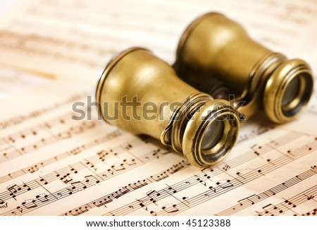 old binoculars on music notes sheet - stock photo