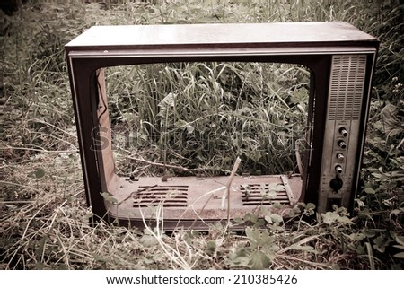 old black and white tv broken in the field, concept of retro and modern, outdoor shot  - stock photo