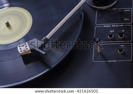 Old black gramophone during playing colorful vinyl plate. Creative close up product macro photography by using long time exposition. - stock photo
