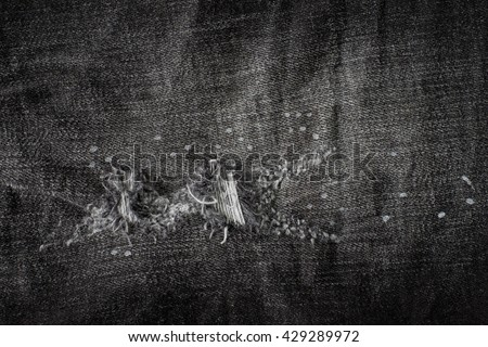 Old black jeans torn denim texture vintage.