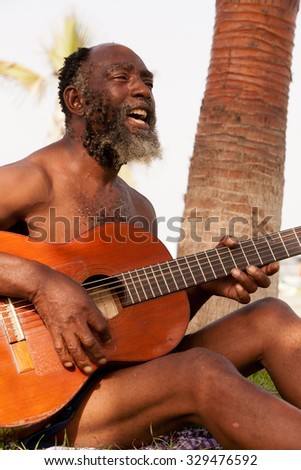 Old Black Men Playing Guitar On A Tropical Island - stock photo