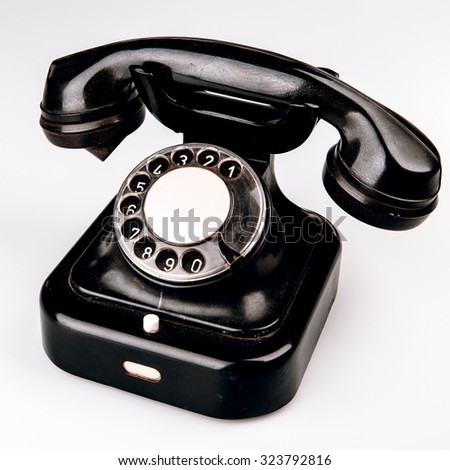 Old black phone with dust and scratches, isolated on white background - retro