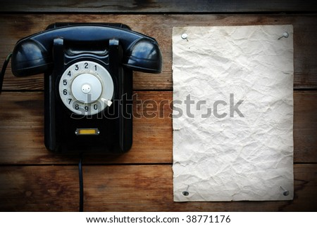 Old black rotary phone and paper. - stock photo