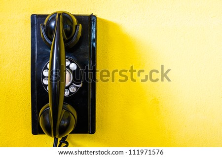 old black telephone with rotary disc on Yellow wall - stock photo