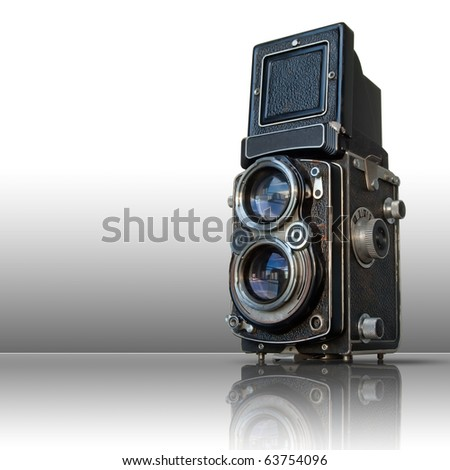 Old black twin lens camera on reflect white floor - stock photo