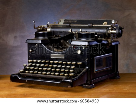 Old black vintage typewriter on a wood counter with neutral background - stock photo
