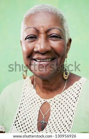 Old black woman portrait, lady in elegant clothes smiling on green background - stock photo