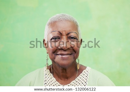 Old black woman portrait, lady in elegant clothes smiling on green background. Copy space - stock photo