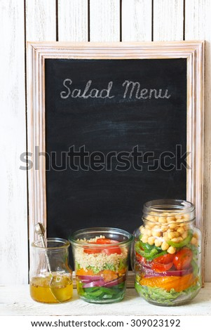 Old blackboard with white chalk and eraser for menu or price and quinoa salad and chickpeas vegetable salad in mason jars with dressing. - stock photo