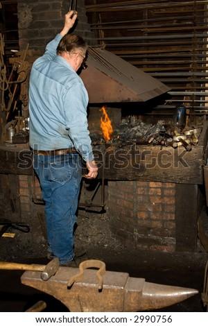 Old Blacksmith at shop. - stock photo